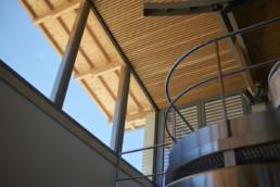 touton architectes - La Commanderie - chais - cuvier - contre plongée passerelle inox et plafond bois ajouré