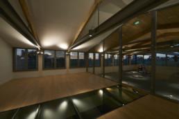 touton architectes - La Commanderie - chais - salle de dégustation de nuit - vue en contrebas chais à barriques - charpente bois et métal