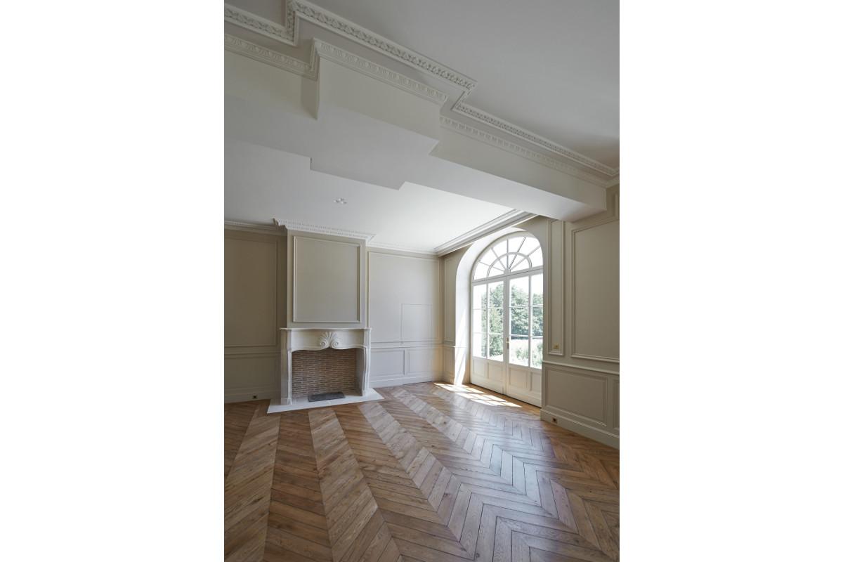 touton architectes - Domaine des Syrtes - rénovation propriété - séjour - parquet bois - cheminée pierre - moulures