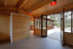 touton architectes - Macreuses - villa - Cap Ferret - cuisine vers terrasse - menuiseries bois - charpente bois apparente