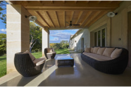 touton architectes - Milord - rénovation - terrasse couverte - salon extérieur - perspective sur jardin - piliers pierre